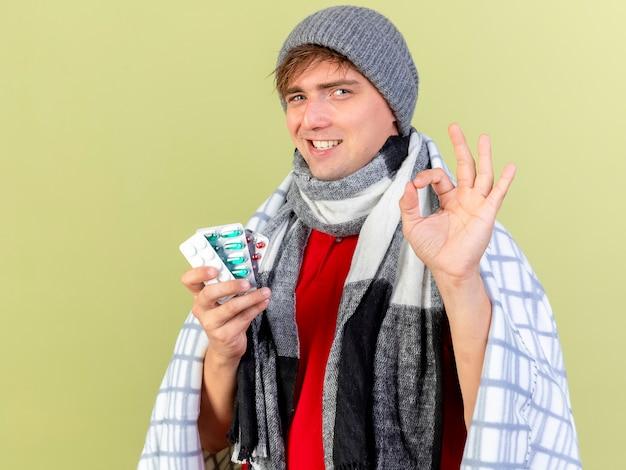 Sorridente giovane uomo malato biondo bello che indossa cappello invernale e sciarpa avvolto in plaid che tiene confezioni di pillole mediche facendo segno ok isolato sulla parete verde oliva con lo spazio della copia