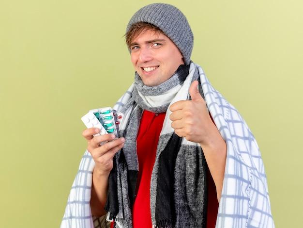 Sorridente giovane uomo malato bello biondo che indossa cappello invernale e sciarpa avvolti in confezioni di plaid che tengono le pillole mediche che mostrano pollice in su isolato sulla parete verde oliva