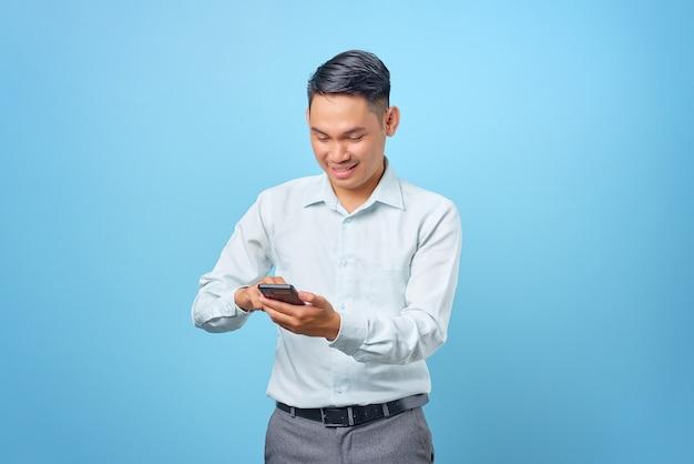 青い背景の上のスマートフォンを使用してテキストメッセージを送る若いハンサムなビジネスマンの笑顔