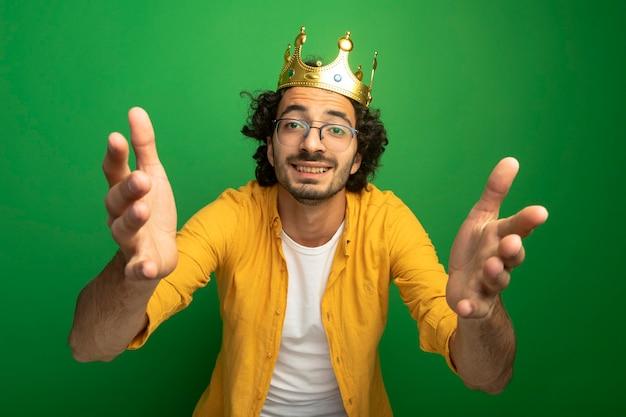 Sorridente giovane uomo caucasico bello con gli occhiali e corona che allunga le mani isolate sulla parete verde