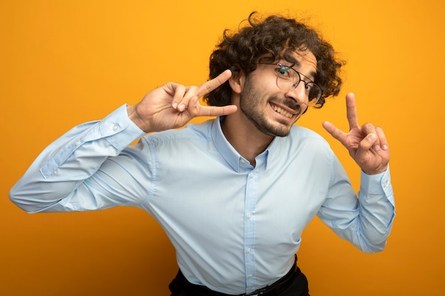 Sorridente giovane uomo caucasico bello con gli occhiali facendo segno di pace isolato sulla parete arancione