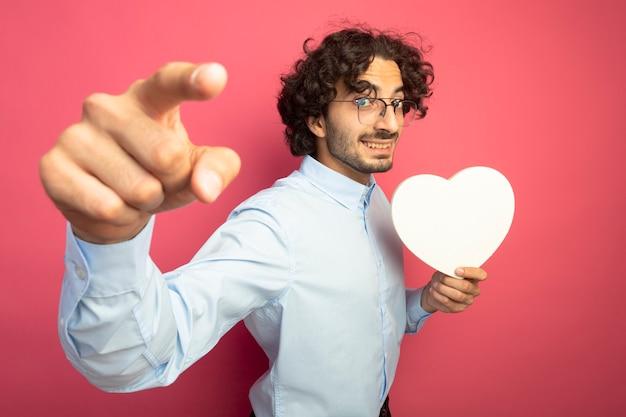 Sorridente giovane uomo caucasico bello con gli occhiali che tengono a forma di cuore guardando e indicando la fotocamera isolata su sfondo cremisi