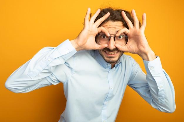 Улыбающийся молодой красивый кавказский мужчина в очках, смотрящий в камеру, делает жест взгляда, используя руки как бинокль, изолированные на оранжевом фоне