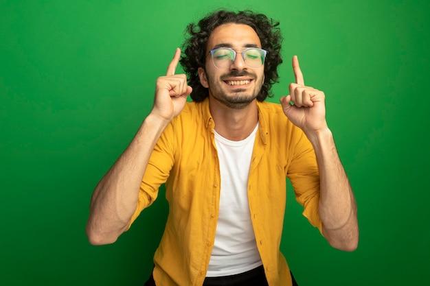 Sorridente giovane uomo caucasico bello con gli occhiali rivolti verso l'alto con gli occhi chiusi isolati su sfondo verde