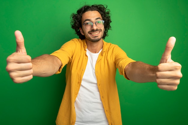 Sorridente giovane uomo caucasico bello con gli occhiali che mostra i pollici in su isolato sulla parete verde