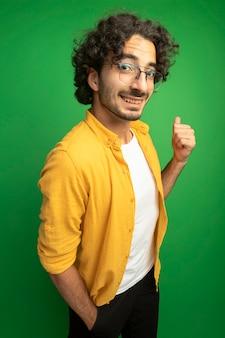 緑の背景で隔離の後ろを指しているポケットに手を保持しているカメラを見て縦断ビューで立っている眼鏡をかけている若いハンサムな白人男性の笑顔