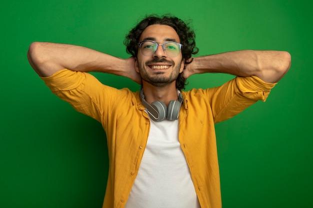 Sorridente giovane uomo caucasico bello con gli occhiali con le cuffie intorno al collo tenendo le mani dietro la testa isolata sulla parete verde