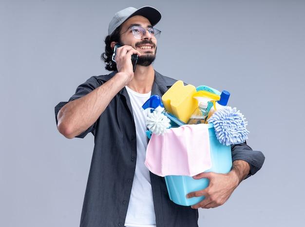 Улыбающийся молодой красивый парень-уборщик в футболке и кепке держит ведро с чистящими средствами и разговаривает по телефону, изолированному на белой стене