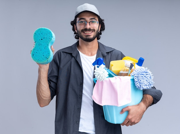 白い壁に分離されたクリーニングツールとスポンジのバケツを保持しているtシャツとキャップを身に着けている若いハンサムなクリーニング男を笑顔