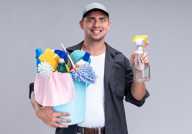 白い壁に分離されたクリーニングツールとスプレーボトルのバケツを保持しているtシャツとキャップを身に着けている若いハンサムなクリーニング男を笑顔