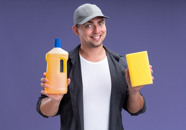 紫色の壁に分離されたスポンジでtシャツとキャップ保持洗浄剤を身に着けている若いハンサムなクリーニング男を笑顔