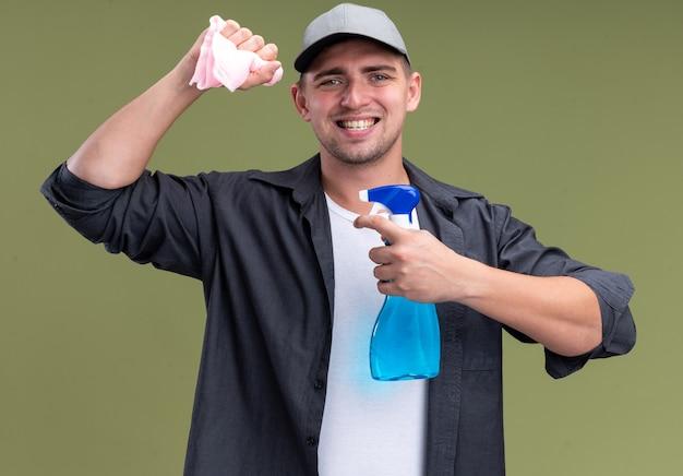 オリーブ グリーンの壁にスプレー ボトルでぼろを保持している t シャツとキャップを着た若いハンサムなクリーニング男の笑みを浮かべてください。