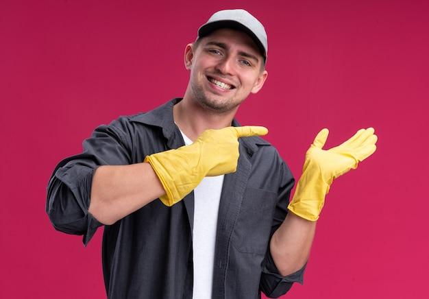 Улыбающийся молодой красивый парень-уборщик в футболке и кепке с перчатками притворяется, что держит, и указывает на что-то изолированное на розовой стене