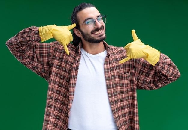 녹색 벽에 고립 된 전화 제스처를 보여주는 티셔츠와 장갑을 끼고 젊은 잘 생긴 청소 남자 미소