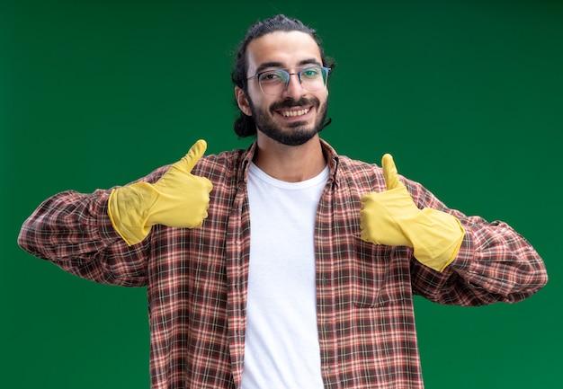 緑の壁に分離された親指を示すtシャツと手袋を身に着けている若いハンサムな掃除人の笑顔