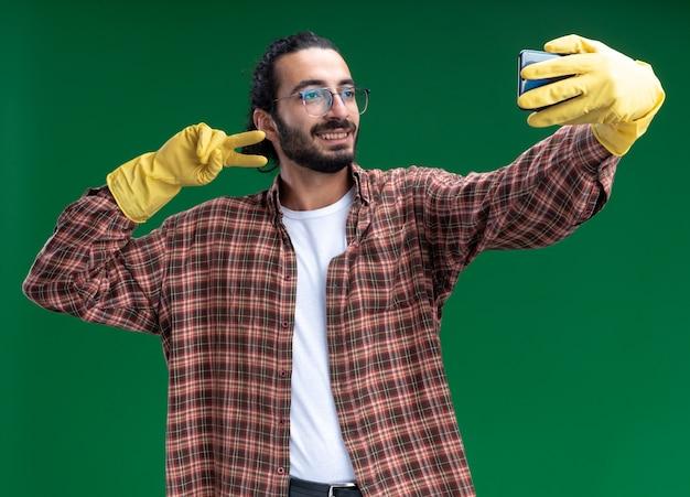 Tシャツと手袋を着た笑顔の若いハンサムな掃除男が、緑の壁に平和のジェスチャーを示す自撮りをする