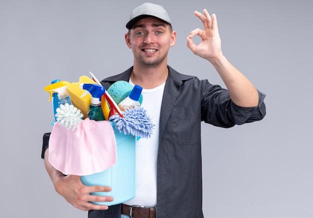 Sorridente giovane bel ragazzo delle pulizie che indossa t-shirt e berretto che tiene secchio di strumenti di pulizia che mostra gesto giusto isolato sulla parete bianca