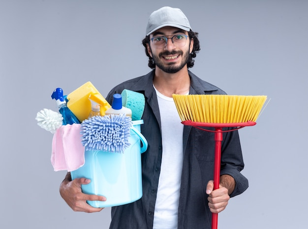 Smiling young handsome cleaning guy wearing t-shirt and cap holding bucket of cleaning tools with mop isolated on white wall
