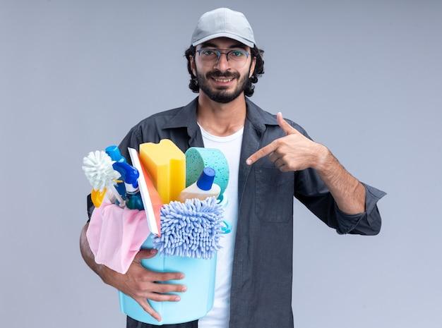 Sorridente giovane bel ragazzo delle pulizie che indossa t-shirt e berretto che tiene e punti al secchio di strumenti di pulizia isolato sulla parete bianca