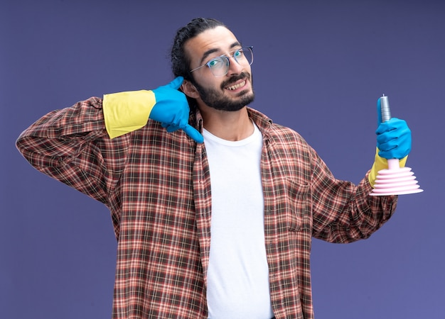 Sorridente giovane bel ragazzo delle pulizie che indossa t-shirt e guanti che tengono lo stantuffo che mostra il gesto della telefonata isolato sul muro blu