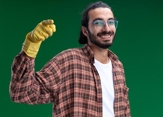Sorridente giovane bel ragazzo delle pulizie indossando t-shirt e guanti punti nella parte anteriore isolata sulla parete verde