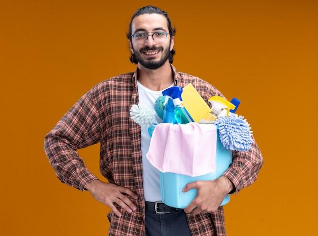 Sorridente giovane bel ragazzo delle pulizie che indossa t-shirt tenendo la benna di strumenti di pulizia mettendo la mano sull'anca isolata sulla parete arancione