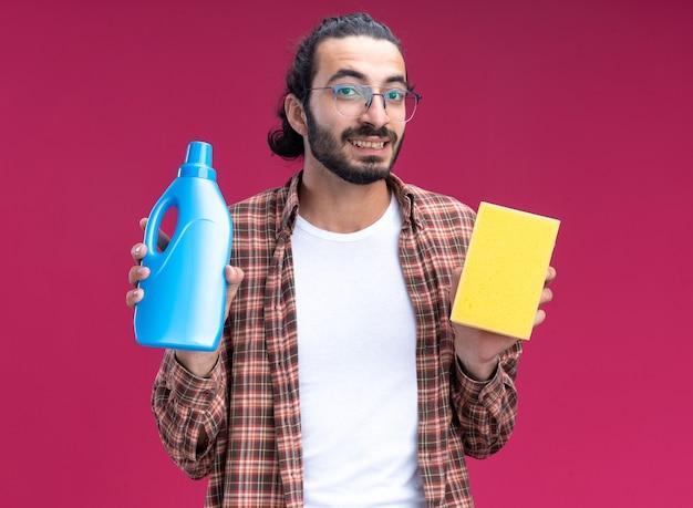 ピンクの壁に分離されたスポンジで洗浄剤を保持しているtシャツを着て笑顔の若いハンサムなクリーニング男