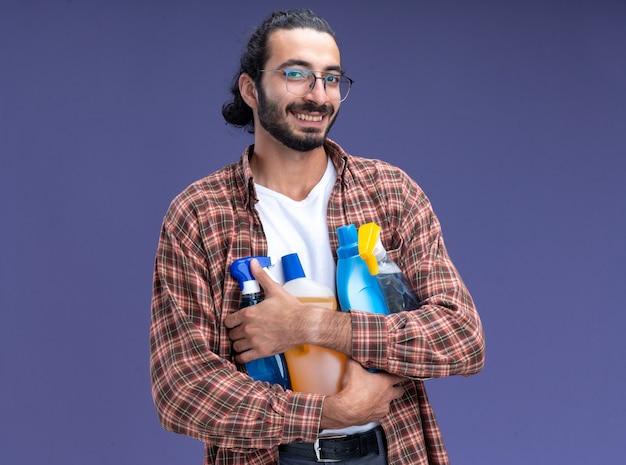 青い壁に分離されたクリーニングツールを保持しているtシャツを着て笑顔の若いハンサムなクリーニング男