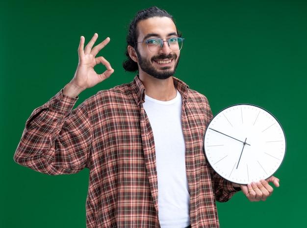 Sorridente giovane ragazzo bello delle pulizie che indossa t-shirt tenendo l'orologio da parete che mostra gesto giusto isolato sulla parete verde