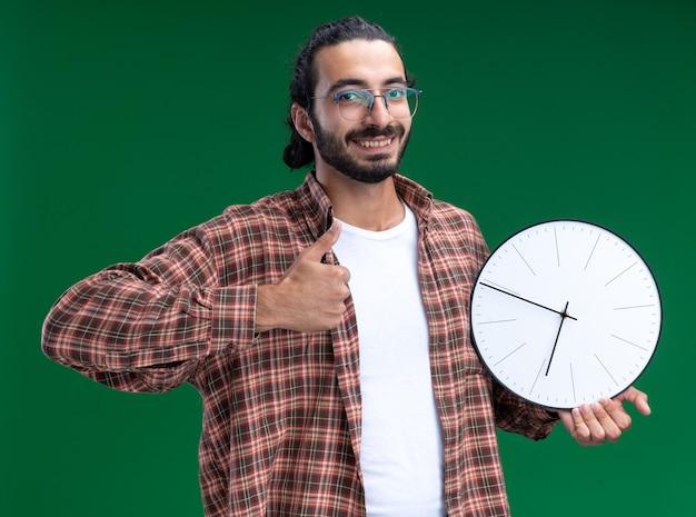 Sorridente giovane bel ragazzo delle pulizie che indossa una t-shirt che tiene l'orologio da parete che mostra il pollice in su isolato sul muro verde