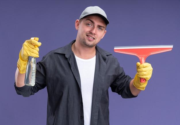 모자와 보라색 벽에 고립 된 걸레 머리와 스프레이 병을 들고 장갑 티셔츠를 입고 젊은 잘 생긴 청소 남자 미소