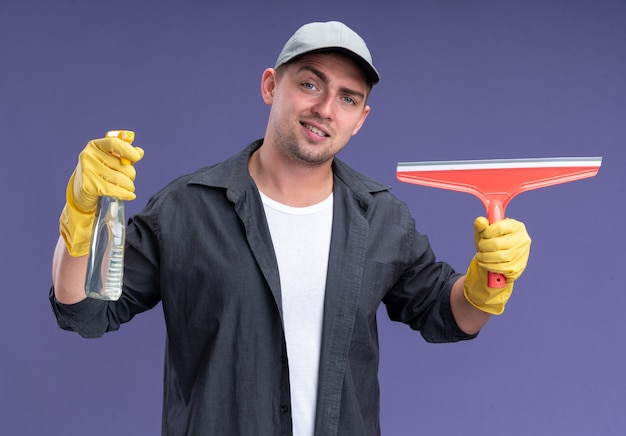 Smiling young handsome cleaning guy wearing t-shirt with cap and gloves holding mop head and spray bottle isolated on purple wall