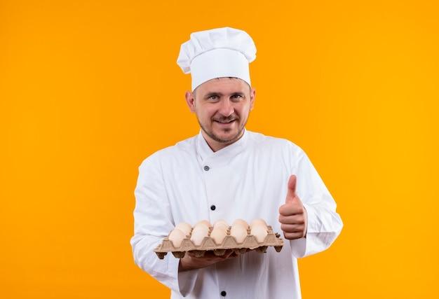 Sorridente giovane cuoco bello in uniforme del cuoco unico che tiene il cartone delle uova e che mostra il pollice in su isolato sullo spazio arancione