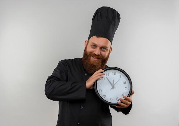 Sorridente giovane cuoco bello in uniforme del cuoco unico che tiene orologio che sembra isolato su spazio bianco