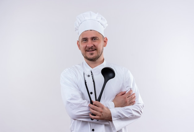 Smiling young handsome cook in chef uniform holding ladle and grill tongs isolated on white space