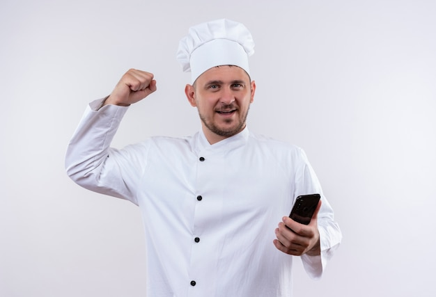 Smiling young handsome cook in chef uniform holding mobile phone and doing strong gesture isolated on white space