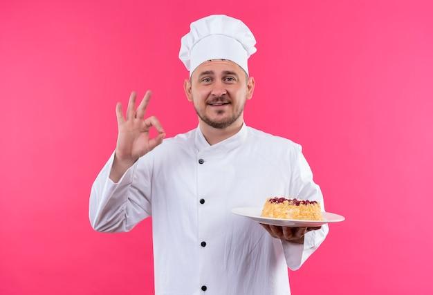 Sorridente giovane cuoco bello in uniforme del cuoco unico che tiene piatto di torta che fa segno giusto isolato sullo spazio rosa