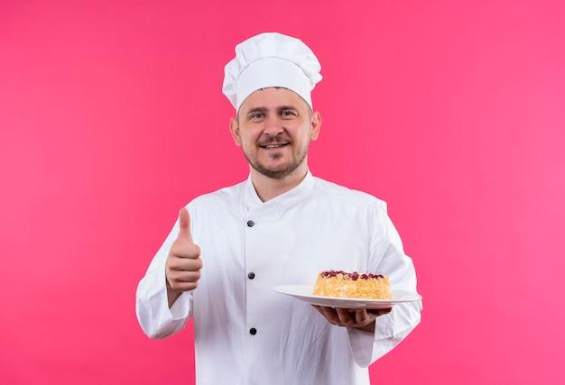 Sorridente giovane cuoco bello in uniforme del cuoco unico che tiene piatto di torta che mostra il pollice in su isolato sullo spazio rosa