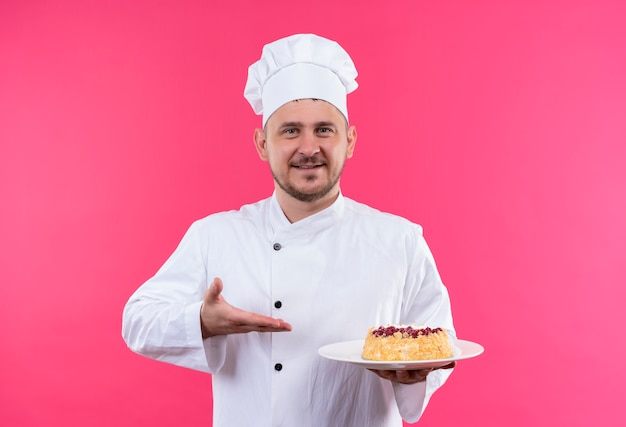 Smiling young handsome cook in chef uniform holding and pointing at plate of cake isolated on pink space