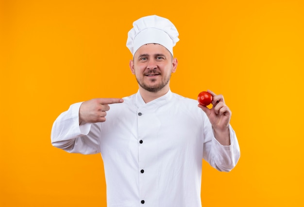 Smiling young handsome cook in chef uniform holding and pointing at tomato isolated on orange space