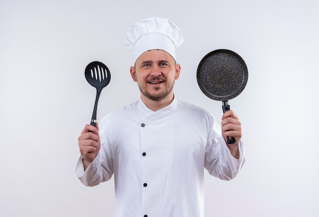 Smiling young handsome cook in chef uniform holding slotted spoon and frying pan on isolated white space