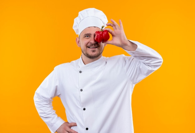 Smiling young handsome cook in chef uniform putting pepper on eye isolated on orange space