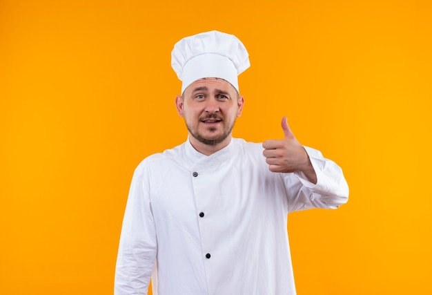 Smiling young handsome cook in chef uniform showing thumb up on isolated orange space