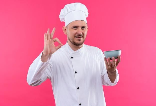 ピンクのスペースで隔離のokサインをやってボウルを保持しているシェフの制服を着た若いハンサムな料理人の笑顔