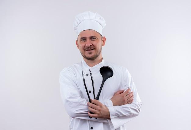 白いスペースで隔離の取鍋とグリルのトングを保持しているシェフの制服を着た若いハンサムな料理人の笑顔