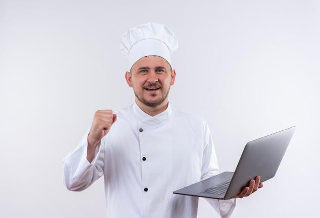 Улыбающийся молодой красивый повар в униформе шеф-повара держит ноутбук и поднимает кулак на изолированном белом пространстве