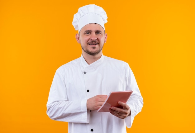 オレンジ色のスペースで隔離のメモ帳を保持しているシェフの制服で若いハンサムな料理人の笑顔