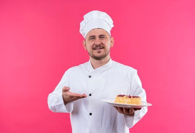 ピンクのスペースで隔離の手でそれを指しているケーキのプレートを保持しているシェフの制服を着た若いハンサムな料理人の笑顔