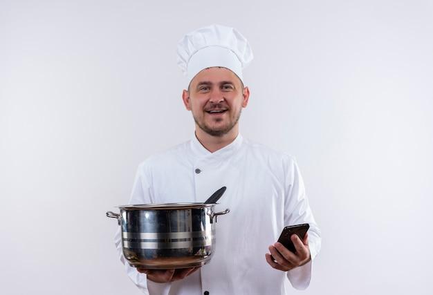 격리 된 공백에 냄비와 휴대 전화를 들고 요리사 유니폼에 젊은 잘 생긴 요리사 미소