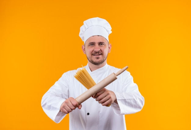 Улыбающийся молодой красивый повар в униформе шеф-повара держит спагетти и скалку, изолированные на оранжевом пространстве